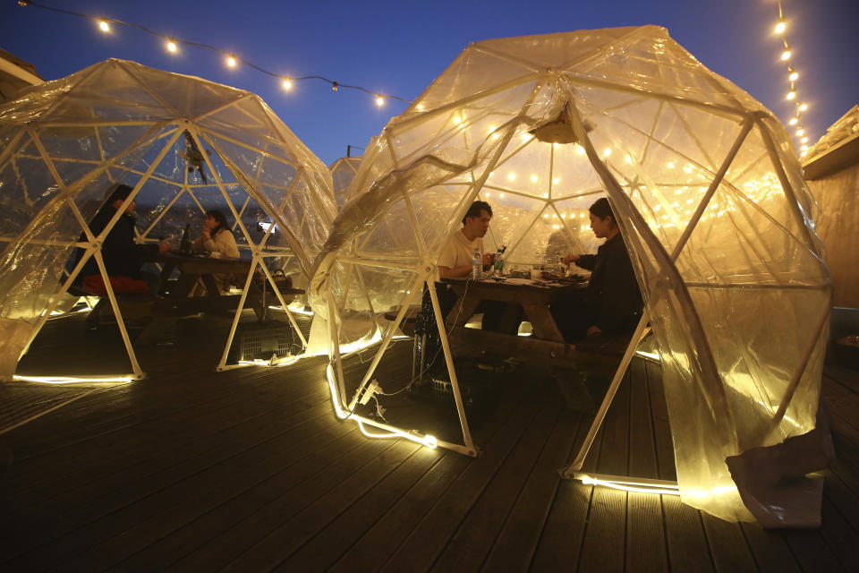 People enjoy outdoor dining at plastic bubbles, observing social distancing against the spread of the coronavirus at a restaurant near the Han River in Seoul, South Korea, Friday, April 9, 2021. (AP Photo/Ahn Young-joon)