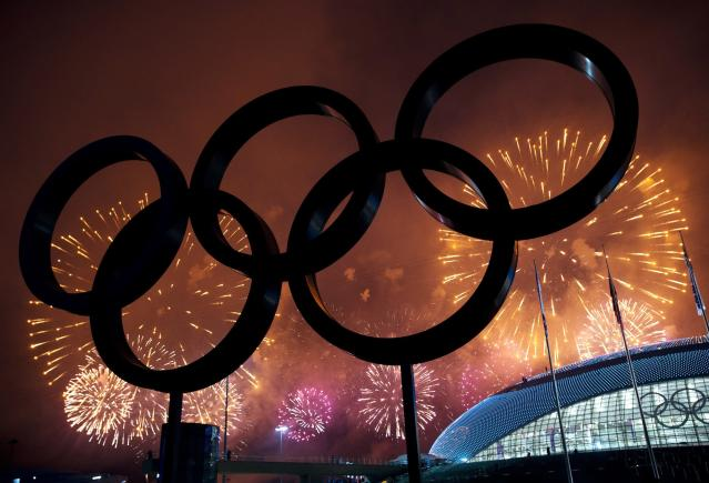 The Olympic Rings are silhouetted as fireworks light up the sky during the closing ceremonies at the 2014 Sochi Winter Olympics on Sunday, Feb. 23, 2014, in Sochi, Russia. (AP Photo/The Canadian Press, Nathan Denette)