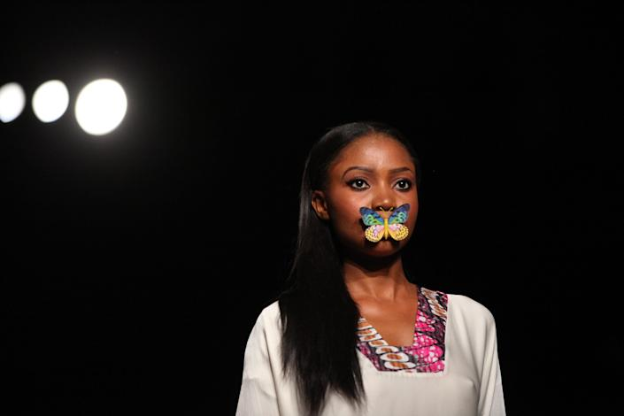 A model has a butterfly over her mouth while wearing an outfit by Eki Orleans at the MTN Lagos Fashion and Design in Lagos, Nigeria, on Friday, Oct. 26, 2012. (AP Photo/Jon Gambrell)