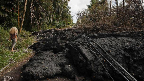 Hannique Ruder, a 65-year-old resident living in the Leilani Estates subdivision, walks past the mound of hardened lava while surveying the neighborhood Friday, May 11, 2018, near Pahoa, Hawaii. (AP)