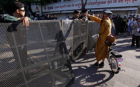 A Buddhist monk tries to enter a blocked street outside the supreme court in Phnom Penh, Cambodia, Thursday, Nov. 16 - Credit: AP