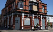 A woman pushes a pram past a closed pub in the Lozells area of Birmingham