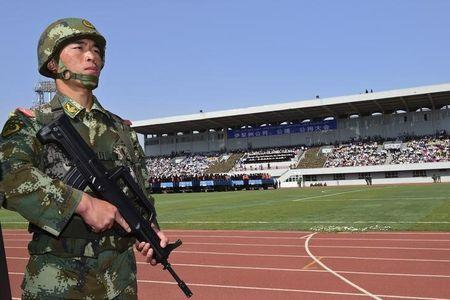 A paramilitary policeman stands guard near trucks carrying criminals and suspects during a mass sentencing rally at a stadium in Yili