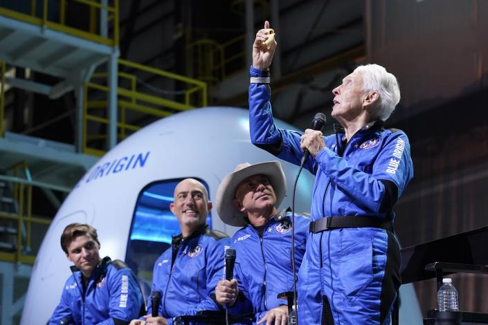 Oliver Daemen, from left, Mark Bezos and Jeff Bezos, founder of Amazon and space tourism company Blue Origin, look on as Wally Funk, right, describes the experience after their launch from the spaceport near Van Horn, Texas, Tuesday, July 20, 2021. (AP Photo/Tony Gutierrez)