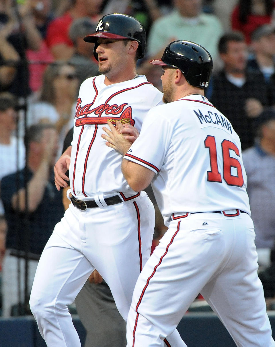 Atlanta Braves' Joey Terdoslavich, left, is congratulated by teammate Brian McCann (16) after they scored on an RBI triple by Elliot Johnson during the second inning of a baseball game against the Cleveland Indians at Turner Field, Tuesday, Aug. 27, 2013, in Atlanta. (AP Photo/David Tulis)
