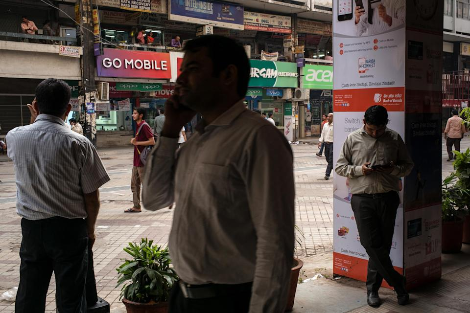 Pedestrians use smartphones at the Nehru Place IT Market in New Delhi, India on Tuesday, May 30, 2017. Reliance Communications Ltd.'s credit rating was cut deeper into junk territory by Moody's Investors Service, which cited its weak operating performance, high leverage and fragile liquidity position. Reliance Communications' troubles come amid intensifying competition among mobile phone carriers in India, fueled by the entry of Reliance Jio, launched by India's richest man Mukesh Ambani. Photographer: Sanjit Das/Bloomberg via Getty Images