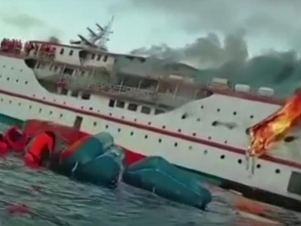 Screengrab from footage shows passengers clambering on board lifeboat as fire rages (NSRA)