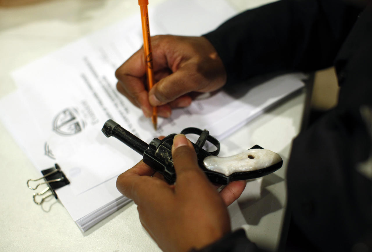 An Evanston police officer documents some information on a firearm that was turned in as part of an amnesty-based gun buyback program in Evanston, Illinois December 15, 2012. Residents were given $100 for each operational firearm given in, and no criminal charges would be laid.    REUTERS/Jim Young (UNITED STATES - Tags: CRIME LAW)