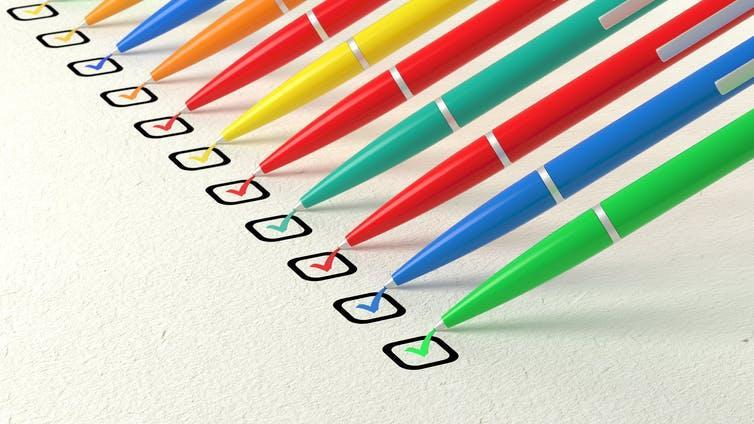 A line of different coloured pens ticking boxes.