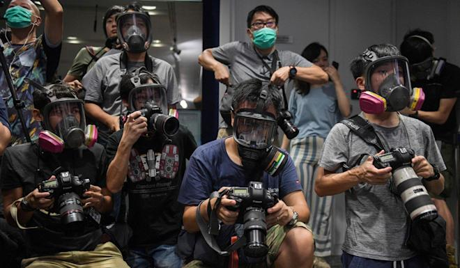 Photojournalists wear gas masks at a police press conference as a protest. Photo: AFP