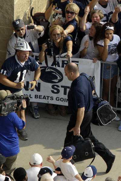 Penn State NCAA college football coach Bill O'Brien carries his bags as he leads his team into Beaver Stadium for their season opener against Ohio in State College, Pa., Saturday, Sept. 1, 2012. (AP Photo/Gene J. Puskar)