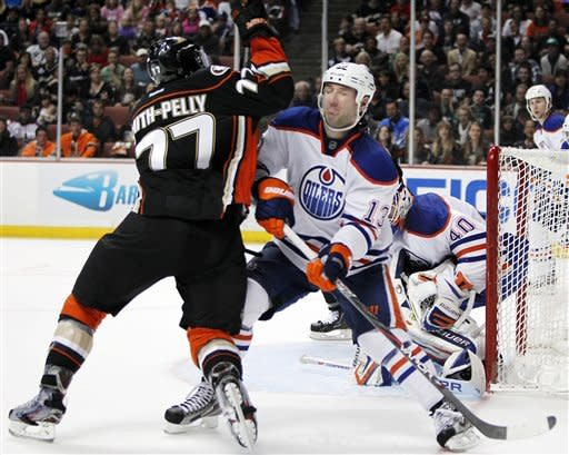 Edmonton Oilers defenseman Cam Barker (13) defends against Anaheim Ducks right wing Devante Smith-Pelly (77) in the second period of an NHL hockey game in Anaheim, Calif., Sunday, April 1, 2012. (AP Photo/Christine Cotter)