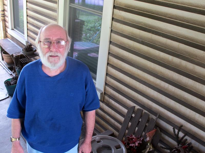 Paul Skoko stands outside his rust-stained house in Georgetown, S.C., in this photograph taken on Friday, Aug. 10, 2012. He was one of a group of local residents who brought a pollution suit against GS Industries, operator of a nearby steel mill, back in 1998 when the company was owned by the company Mitt Romney co-founded, Bain Capital. (AP Photo/Bruce Smith).