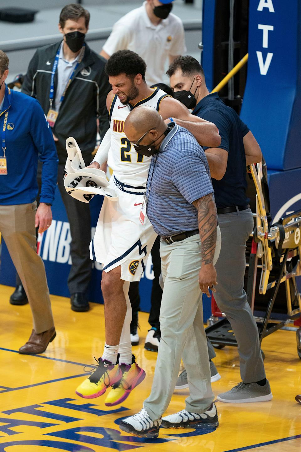 Nuggets guard Jamal Murray is helped off the court by a trainer.