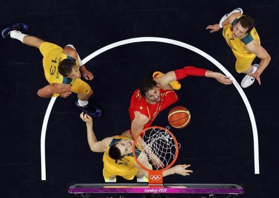 Spain's Pau Gasol (C) fights for the ball next to Australia's players during the men's preliminary round Group B basketball match at the Basketball Arena during the London 2012 Olympic Games July 31, 2012.