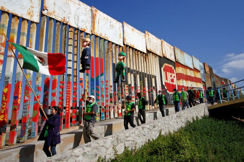 Migrants and members of civil society hold pinatas during a protest in Tijuana