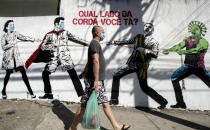 "A man, wearing a protective face mask as a measure to curb the spread of the new coronavirus, walks past a mural depicting a tug-of-war between health workers and Brazil's President Jair Bolsonaro aided by a cartoon-styled coronavirus character, with a message that reads in Portuguese: ""Which side are you on?,"" in Sao Paulo, Brazil, Friday, June 19, 2020. (AP Photo/Andre Penner)"