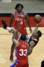 Houston Rockets forward DaQuan Jeffries, right, falls backward on his shot attempt between Philadelphia 76ers guard Tyrese Maxey (0) and guard George Hill (33) during the second half of an NBA basketball game Wednesday, May 5, 2021, in Houston. (AP Photo/Michael Wyke, Pool)