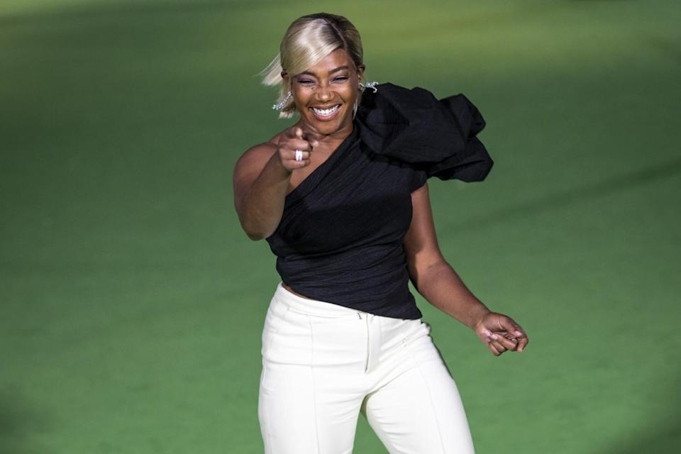 A woman pointing in a black shirt and white pants on a green carpet