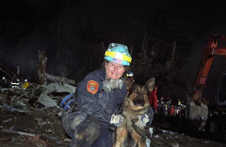 A firefighter holds a search and rescue dog which was used to hunt for survivors. (Caters)