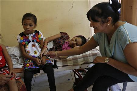 Rekha Patel (R), 42, from Britain, touches surrogate mother Naina Patel's (C) biological daughter inside a temporary home for surrogates provided by Akanksha IVF centre in Anand town, about 70 km (44 miles) south of the western Indian city of Ahmedabad August 25, 2013. REUTERS/Mansi Thapliyal