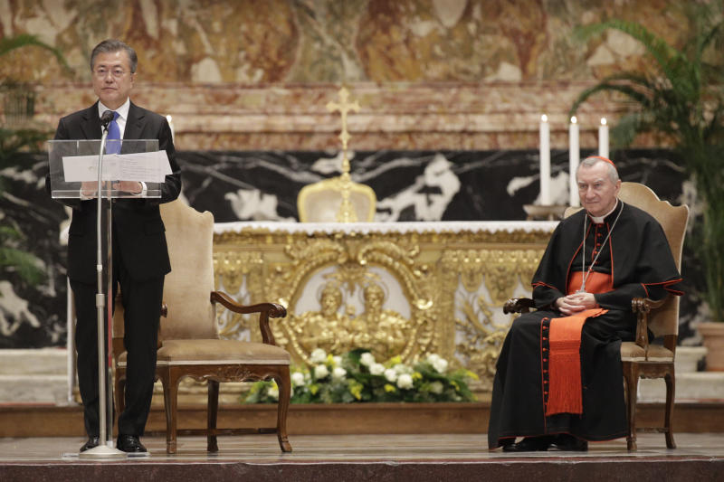 Vatican Secretary of State Pietro Parolin, right, listens to South Korean President Moon Jae-in delivering a speech at the end of a Mass for peace inside St. Peter's Basilica at the Vatican, Wednesday, Oct. 17, 2018. South Korea's president is in Italy for a series of meetings that will culminate with an audience with Pope Francis at which he's expected to extend an invitation from North Korean leader Kim Jong Un to visit. (AP Photo/Gregorio Borgia)