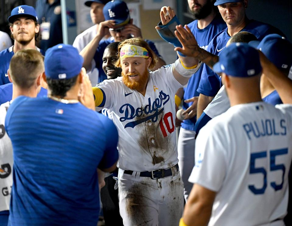 Dodgers third baseman Justin Turner (10) gets high fives in the dugout after scoring a run in the eighth inning against the Braves at Dodger Stadium.