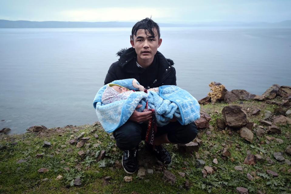 File - In this Thursday, March 5, 2020, file photo, a migrant holding a baby pauses on the side of the road while walking to the village of Skala Sikaminias, on the Greek island of Lesbos, after crossing on a dinghy the Aegean sea from Turkey. The European Union's border and coast guard is under pressure following a series of allegations that it was involved in illegal pushbacks of migrants. Frontex is an increasingly powerful agency that monitors the 27-nation bloc's external borders. (AP Photo/Alexandros Michailidis, File)
