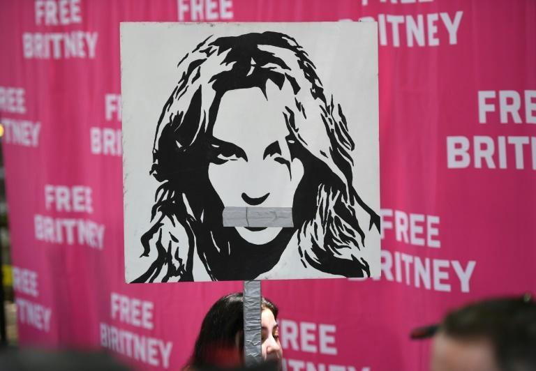 A woman holds a poster of Britney with her mouth taped shut as fans and supporters gather outside the Los Angeles County Courthouse in Los Angeles on July 14, 2021