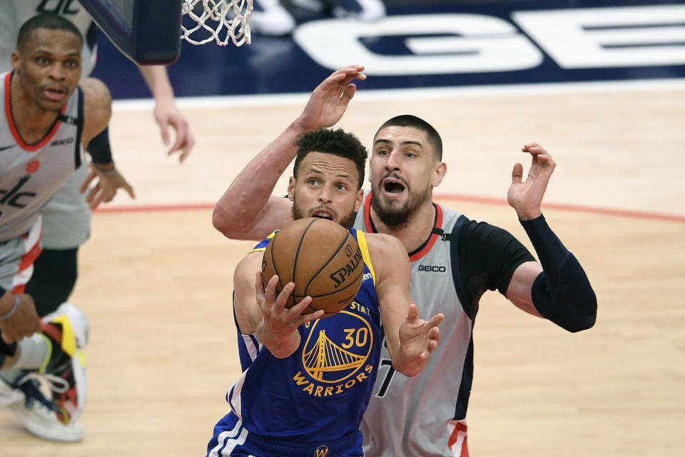 Golden State Warriors guard Stephen Curry (30) goes to the basket past Washington Wizards center Alex Len, back, during the second half of an NBA basketball game, Wednesday, April 21, 2021, in Washington. (AP Photo/Nick Wass)