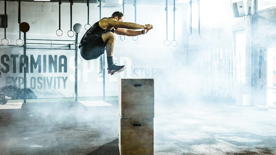 Athletic man jumping on a crate while having sports training in a gym.