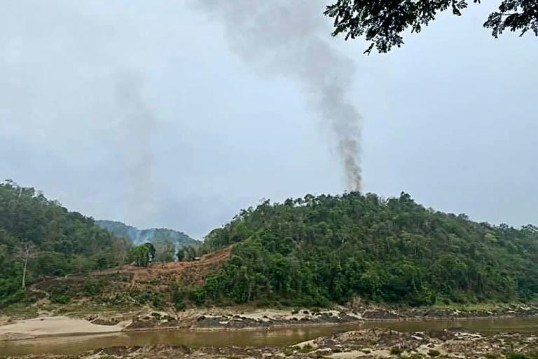 This handout taken and released on April 27, 2021 shows smoke rising from a Myanmar military base, as seen from Mae Sam Laep in Thailand, after the base was captured by the Karen National Union