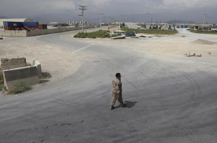 """A member of the Afghan security forces walks in the sprawling Bagram air base after the American military departed, in Parwan province north of Kabul, Afghanistan, Monday, July 5, 2021. The U.S. left Afghanistan's Bagram Airfield after nearly 20 years, winding up its """"forever war,"""" in the night, without notifying the new Afghan commander until more than two hours after they slipped away. (AP Photo/Rahmat Gul)"""