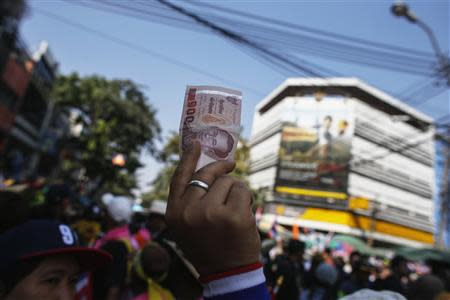 An anti-government protester holds up Thai banknote to donate to anti-government protest leader Suthep Thaugsuban during rally in central of Bangkok
