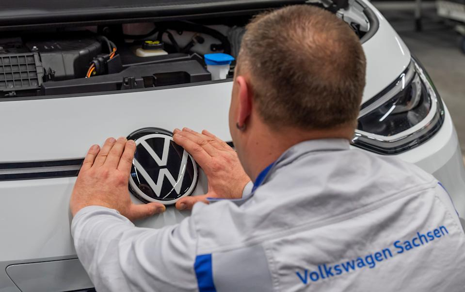 FILE PHOTO: An employee fixes a VW sign at a production line of the electric Volkswagen model ID.3 in Zwickau, Germany, February 25, 2020. REUTERS/Matthias Rietschel