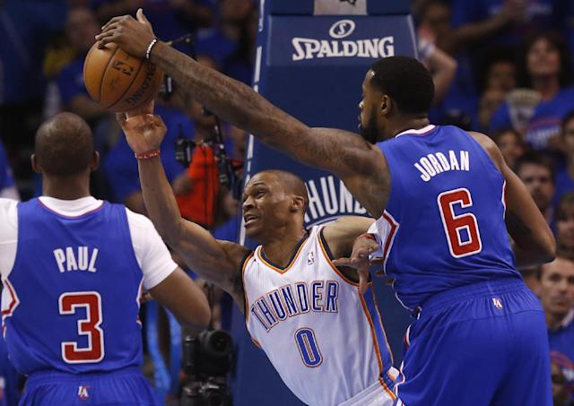 Los Angeles Clippers center DeAndre Jordan (6) blocks a pass by Oklahoma City Thunder guard Russell Westbrook (0) in the first quarter of Game 1 of the Western Conference semifinal NBA basketball playoff series in Oklahoma City, Monday, May 5, 2014. (AP Photo/Sue Ogrocki)