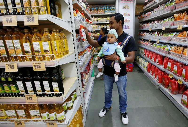 A customer carries his daughter as he buys goods at a store inside a shopping mall in Kolkata
