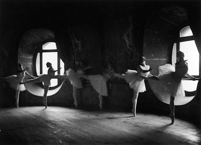 Ballerinas at barre against round windows during rehearsal for Swan Lake at Grand Opera de Paris.