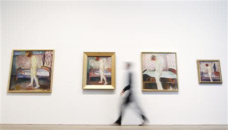 """Holden of the Tate poses with four paintings of Edvard Munch's """"Weeping Woman"""" series at the Tate Modern in London's Southbank"""