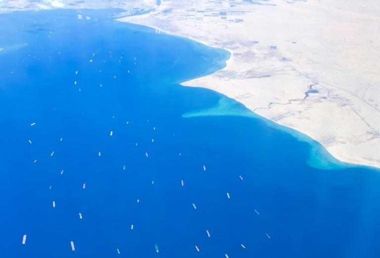 An aerial view taken from the porthole of a commercial plane shows ships stranded in the Red sea, as the MV 'Ever Given' (Evergreen) container ship continues to block the Suez Canal in both directions