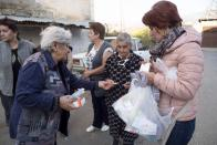 Volunteer doctor Eleonora Ovanesyan, right, distributes drugs to women near their apartment building during a military conflict in Stepanakert, the separatist region of Nagorno-Karabakh, Friday, Oct. 16, 2020. Nagorno-Karabakh, which lies within Azerbaijan but has been under the control of ethnic Armenian forces since a war there ended in 1994, faces an outbreak of the coronavirus amid the largest outbreak of hostilities in more than a quarter-century. (AP Photo)