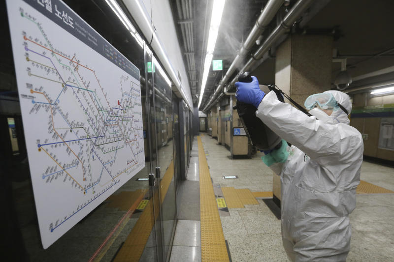 "A worker wearing protective gears sprays disinfectant as a precaution against the coronavirus at a subway station in Seoul, South Korea, Friday, Feb. 21, 2020. South Korea on Friday declared a ""special management zone"" around a southeastern city where a surging viral outbreak, largely linked to a church in Daegu, threatens to overwhelm the region's health system. (AP Photo/Ahn Young-joon)"