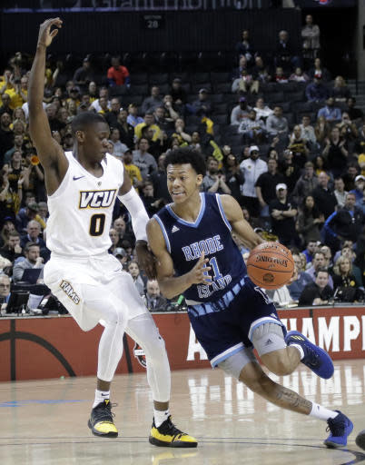 Rhode Island's Jeff Dowtin (11) drives past VCU's De'Riante Jenkins (0) during the second half of an NCAA college basketball game in the Atlantic 10 men's tournament Friday, March 15, 2019, in New York. Rhode Island won 75-70. (AP Photo/Frank Franklin II)