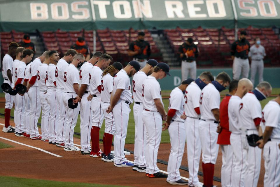 The Boston Red Sox and the Baltimore Orioles line up on the base lines during a moment of silence for lives lost to COVID-19, before an opening day baseball game at Fenway Park, Friday, July 24, 2020, in Boston. (AP Photo/Michael Dwyer)