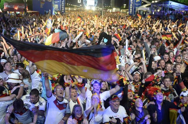 Fans of Germany celebrate as they watch the 2014 World Cup final between Germany and Argentina in Brazil at a public screening of the match in Berlin July 13, 2014. REUTERS/Fabian Bimmer (GERMANY - Tags: SPORT SOCCER)