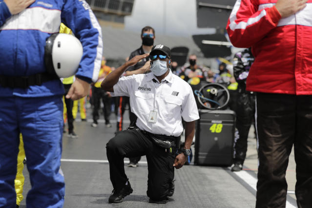 A NASCAR official kneels during the national anthem before a NASCAR Cup Series auto race at Atlanta Motor Speedway on Sunday, June 7, 2020, in Hampton, Ga. NASCAR paused before Sundays Cup race at Atlanta Motor Speedway to acknowledge the countrys social unrest. (AP Photo/Brynn Anderson)