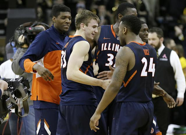 Illinois forward Jon Ekey, center, celebrates with teammates at the end of an NCAA college basketball game against Iowa, Saturday, March 8, 2014, in Iowa City, Iowa. Ekey made a 3-point basket in the final seconds to give Illinois a 66-63 victory. (AP Photo/Charlie Neibergall)