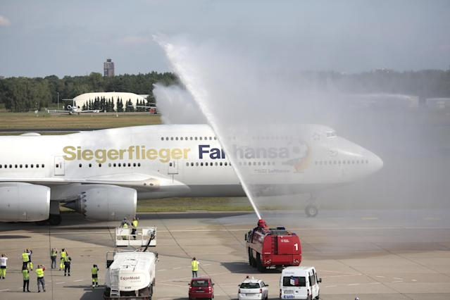 "The plane with the players of German national soccer team arrives at Tegel airport in Berlin Tuesday, July 15, 2014. Germany's World Cup-winning team has returned home from Brazil to celebrate the country's fourth title with huge crowds of fans. The team's Boeing 747 touched down at Berlin's Tegel airport midmorning Tuesday after flying a lap of honor over the ""fan mile"" in front of the landmark Brandenburg Gate. Words on plane read: Winner Plane and instead of Lufthansa, Fanhansa. (AP Photo/Markus Schreiber)"