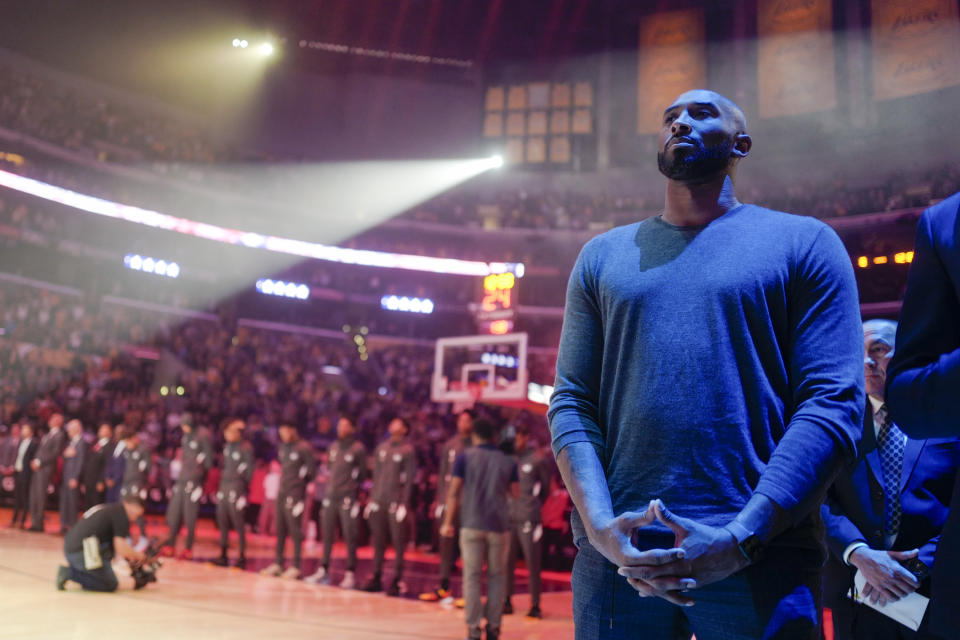 Former Los Angeles Lakers Kobe Bryant listens to the national anthem prior to an NBA basketball game between Los Angeles Lakers and Atlanta Hawks, Sunday, Nov. 17, 2019, in Los Angeles. The Lakers won 122-101. (AP Photo/Ringo H.W. Chiu)