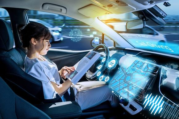 A woman reads a book in a driverless vehicle.